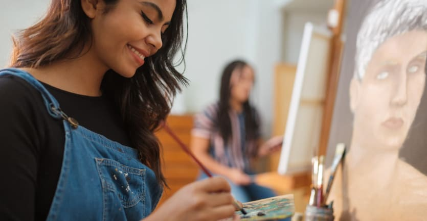 A smiling student in a black shirt and overalls mixes paints on a palette while working on a painting.