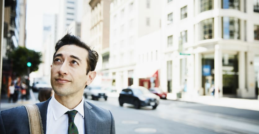 A man in a suit and tie and pocket square looks upward with a hopeful expression on an urban street.