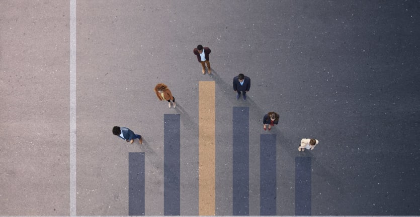 An overhead shot of a group of people shows them each standing at the pinnacle of a bar graph etched into the floor.