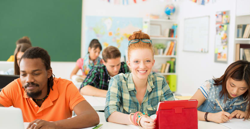 A redheaded woman in a plaid flannel shirt and numerous bracelets sits at a desk in a college classroom surrounded by fellow students and smiles at the camera.