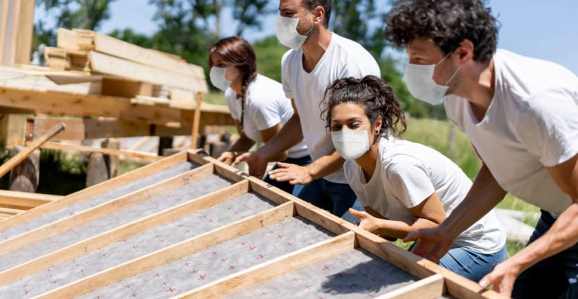 Four young adult volunteers in matching blue jeans, white t-shirts, and face masks work together to hoist up the wall of a home the group is building.