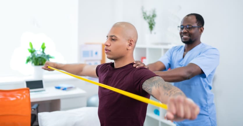 An athlete stretches a yellow rubber band across his chest while a physical therapist places his hands on the athlete's shoulders.