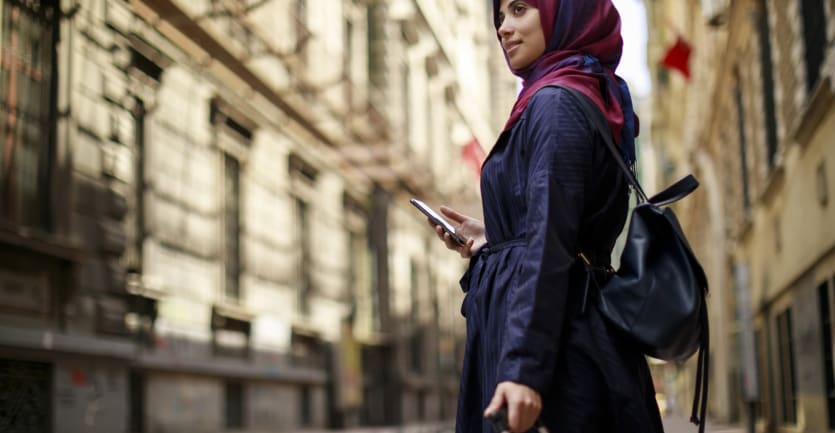 A young woman donning a pink and purple headscarf and a black backpack stands in the middle of a city, holding a cell phone in one hand and clutching a suitcase with the other.