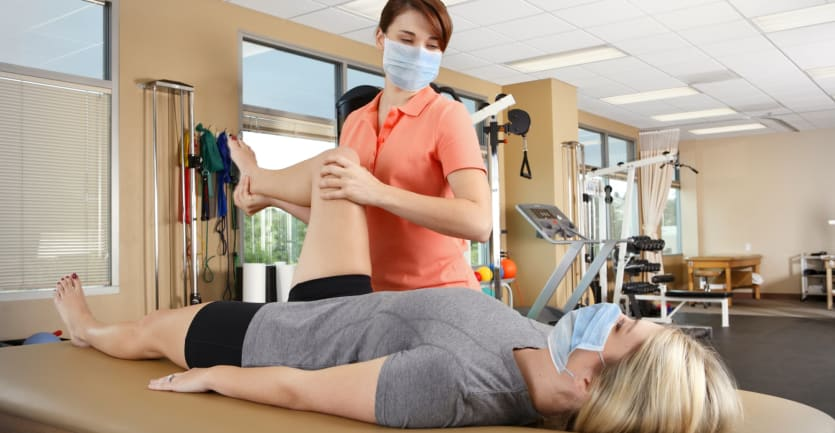 A physical therapist helps stretch the leg of a patient lying down on an examination table in a large, well lit room.