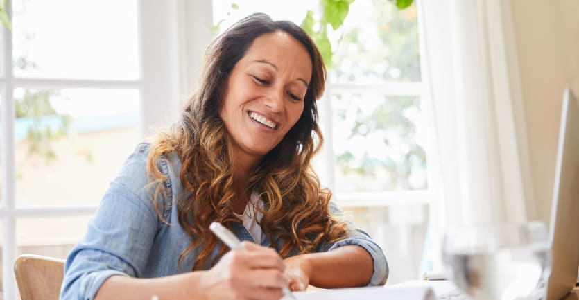 A woman in a denim shirt with rolled-up sleeves, sitting at her kitchen table, smiles as she takes hand-written notes next to her laptop computer.