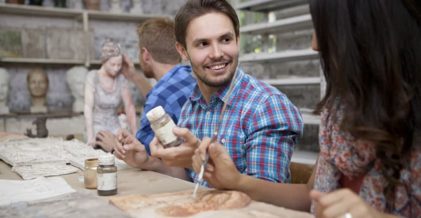 A man in a brightly colored plaid shirt smiles as he chats with a fellow student while seated at a table in a pottery studio.