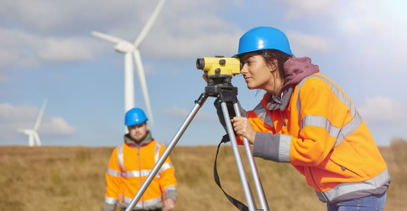 A woman in an orange jacket and blue hardhat peers through the scope of a level as her coworker walks toward her through an open field, wind turbines churning in the background.