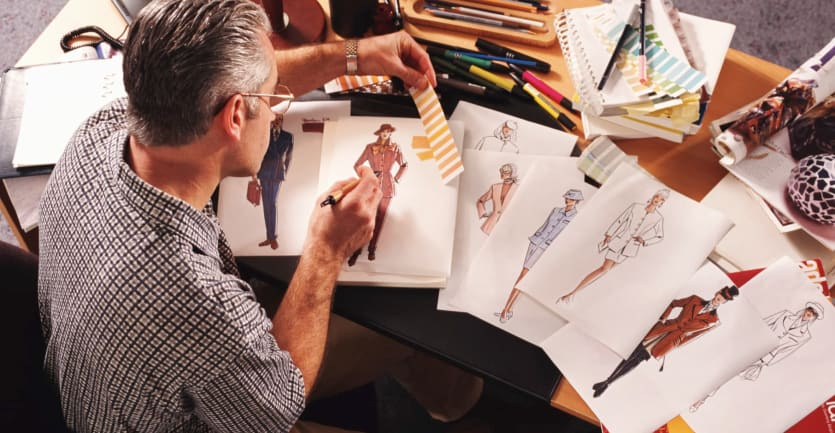 A top-down shot of a bespectacled man in a checkered short-sleeved collared shirt sketching out fashion designs on a busy desk.