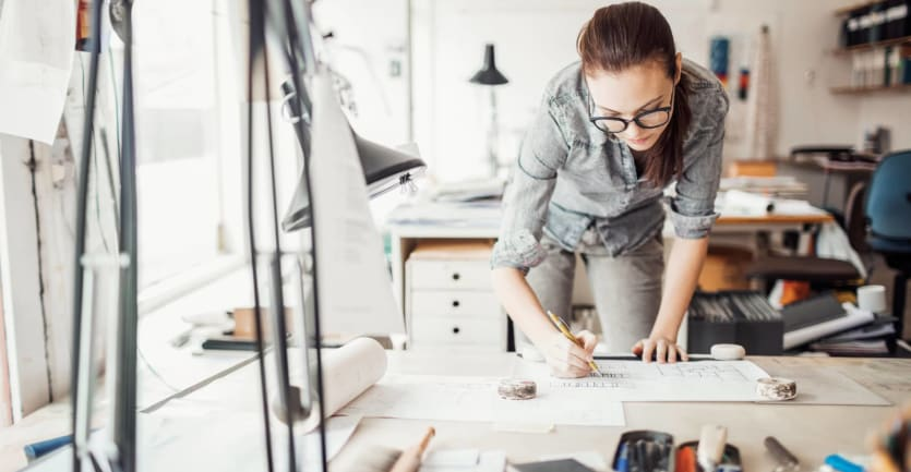 A woman wearing glasses, in gray denim jeans and a shirt with rolled up sleeves, leans over her desk to look at architectural plans.