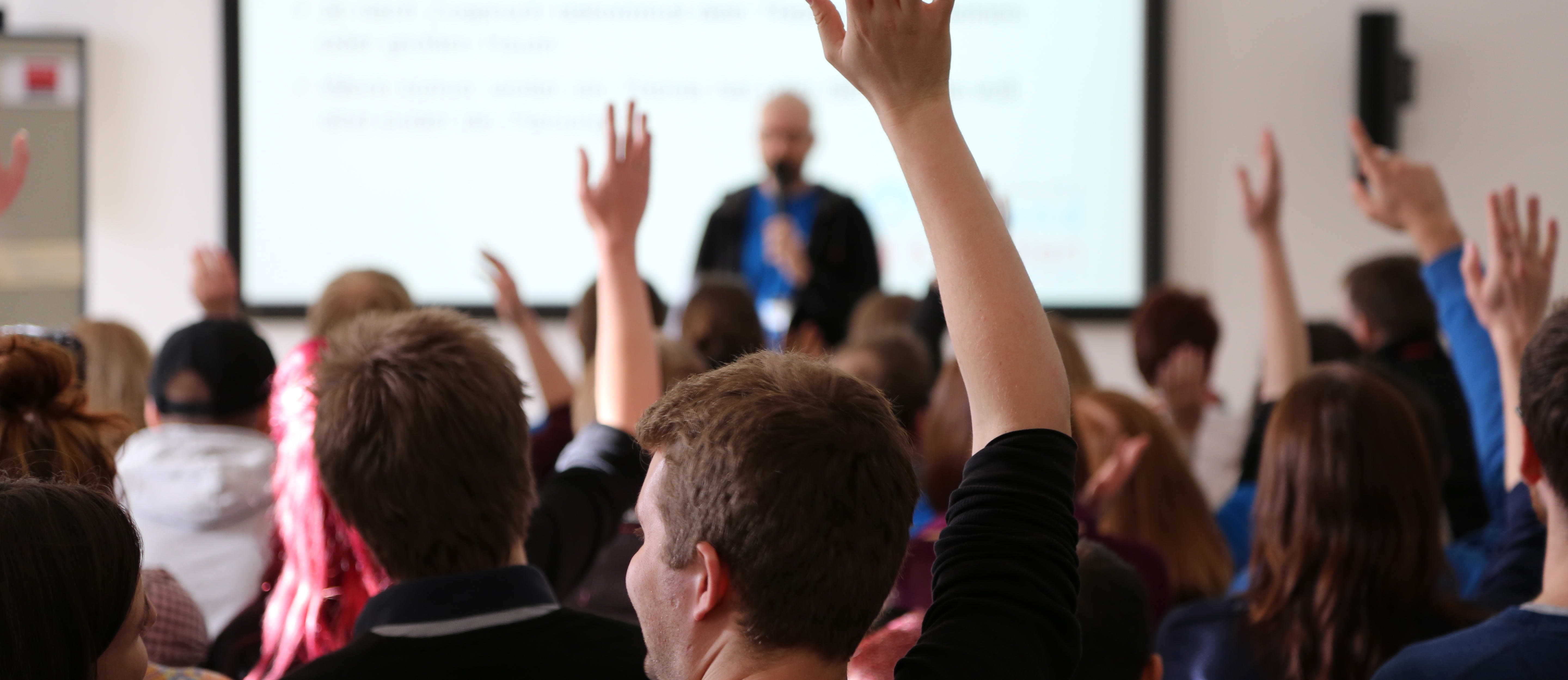 A group of students in a classroom raise their hands