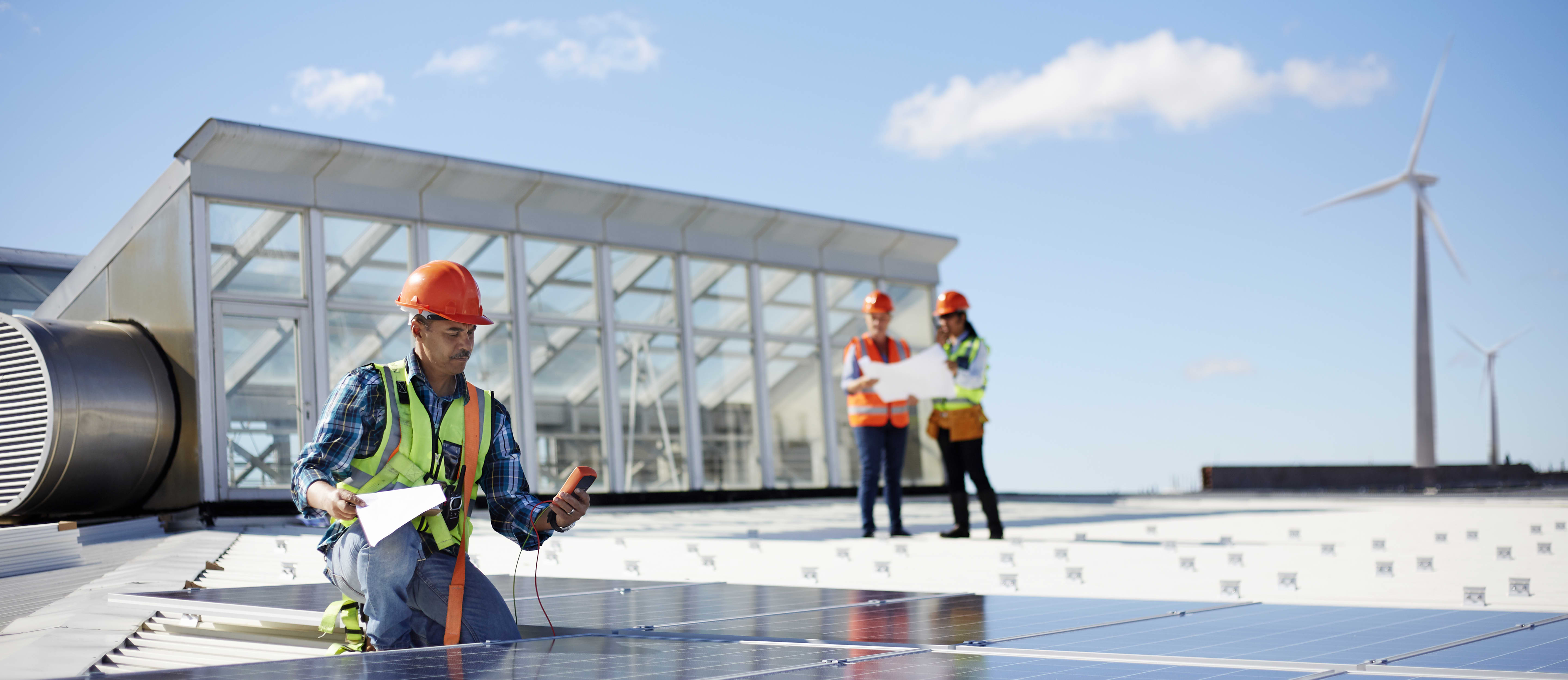 A group of engineers in hard hats test solar panels
