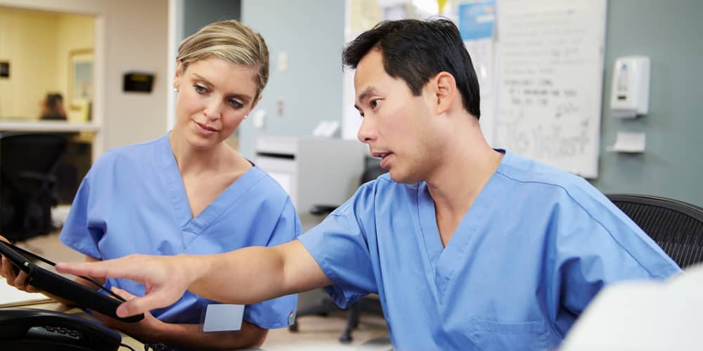 Two nurses discussing work at nurse station in hospital