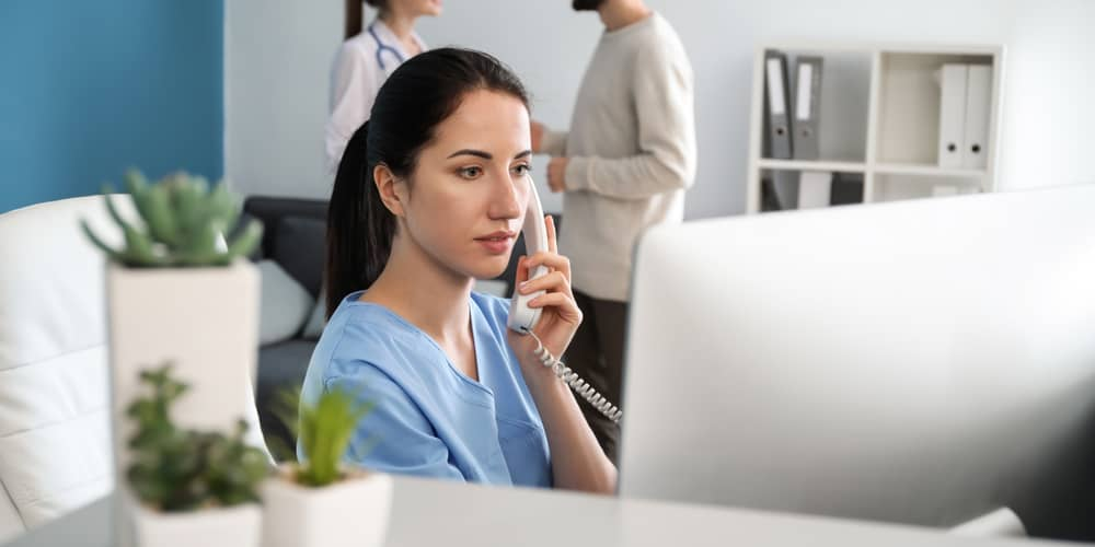 A hospital administrator in front of a computer speaking on the phone - Image