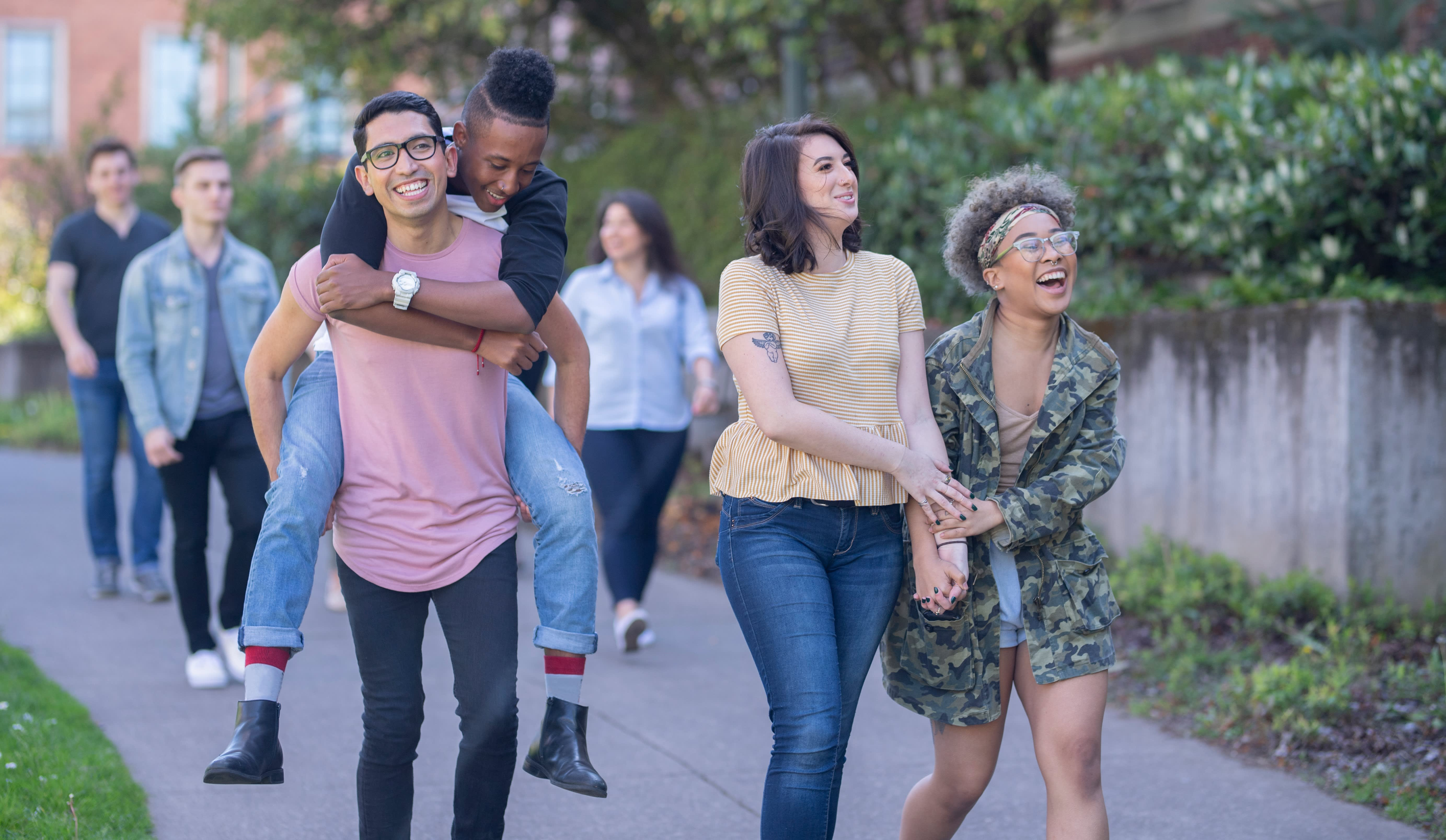 Two couples walk through a college campus, with one doing a piggy back ride