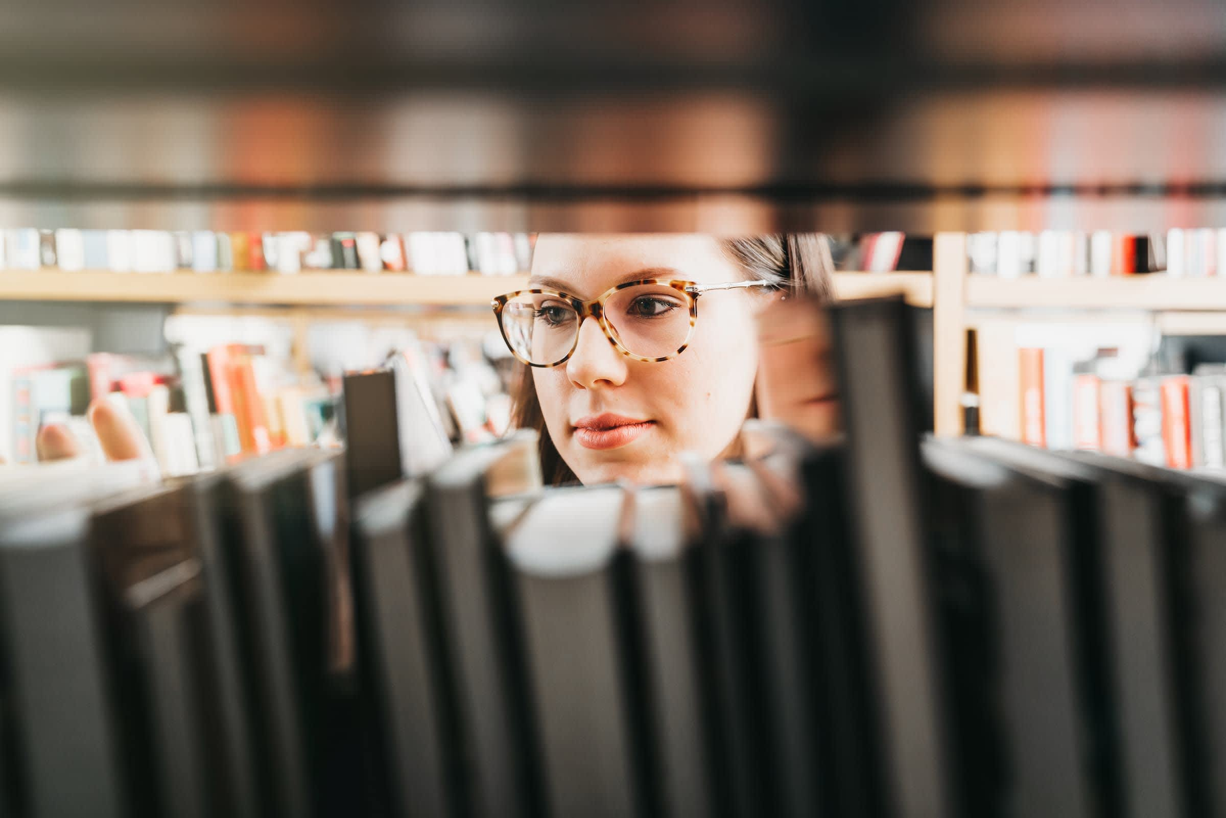 Image of student in library looking through a shelf of books
