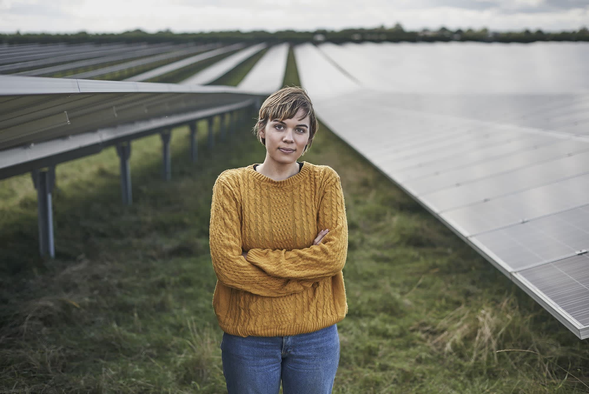 young female farmer stands in field of solar panels