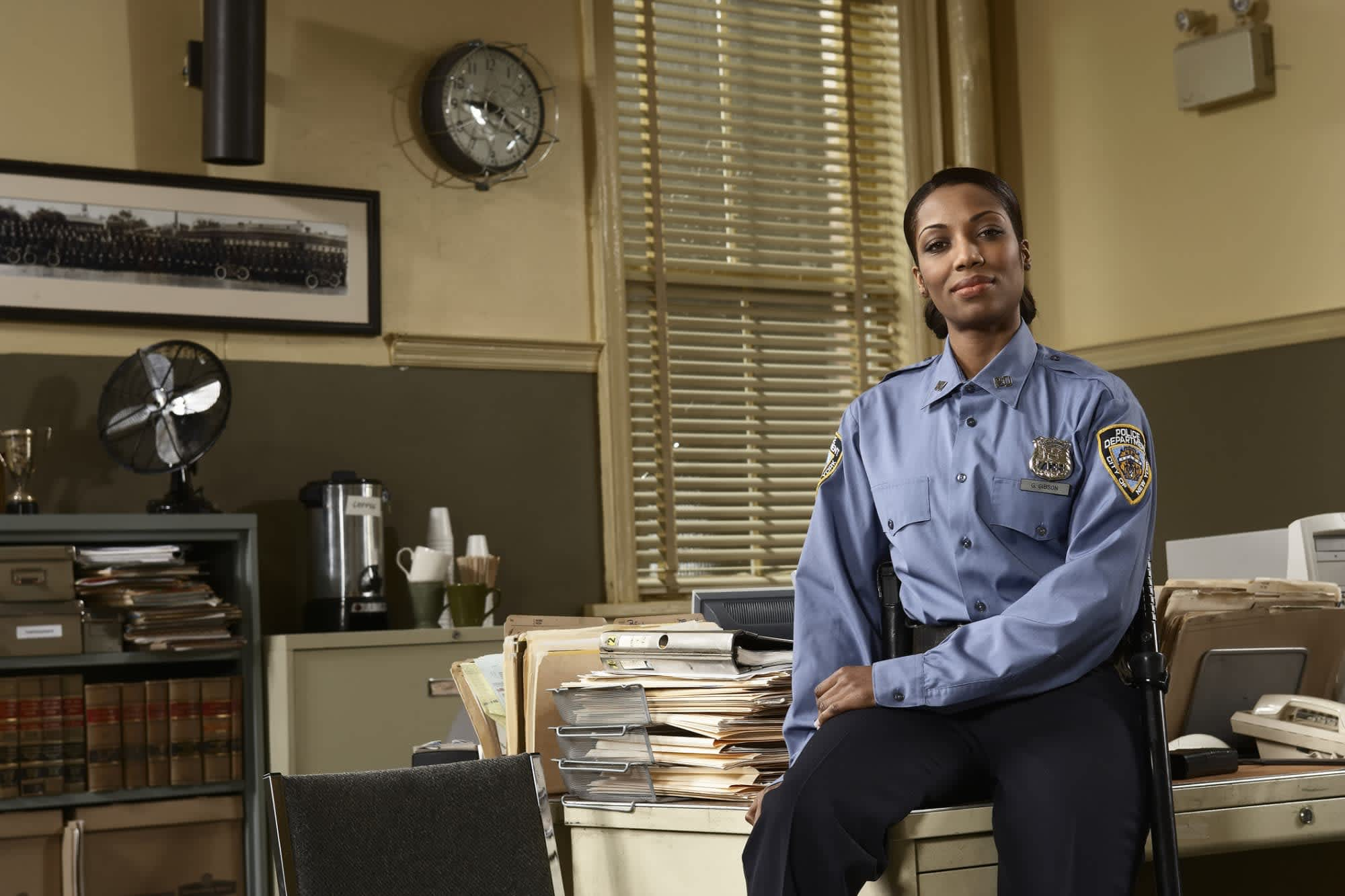 black female cop sitting on a desk of file folders and police work