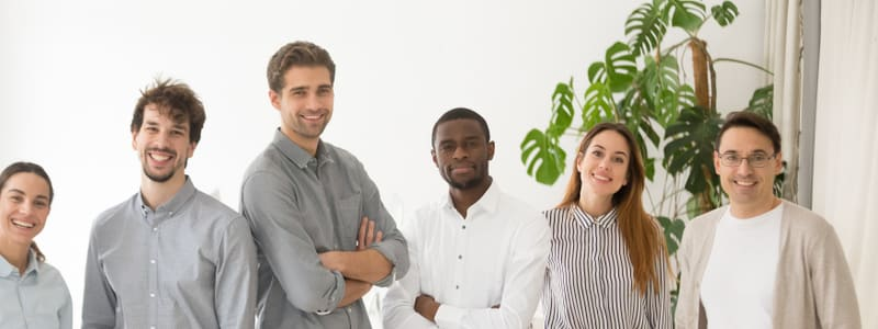 Young happy multiracial professionals or company staff looking at camera smiling, multi-ethnic group of diverse business people standing together.