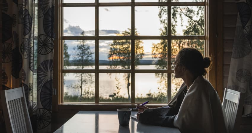 A person sitting at a table with a notebook stares out the window at a lake