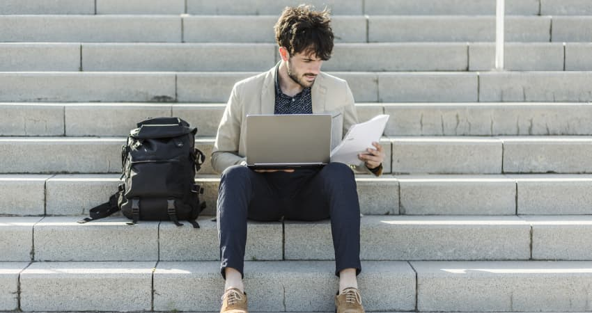 A student sits on cement stairs with his backpack and laptop, looking at a printed resume