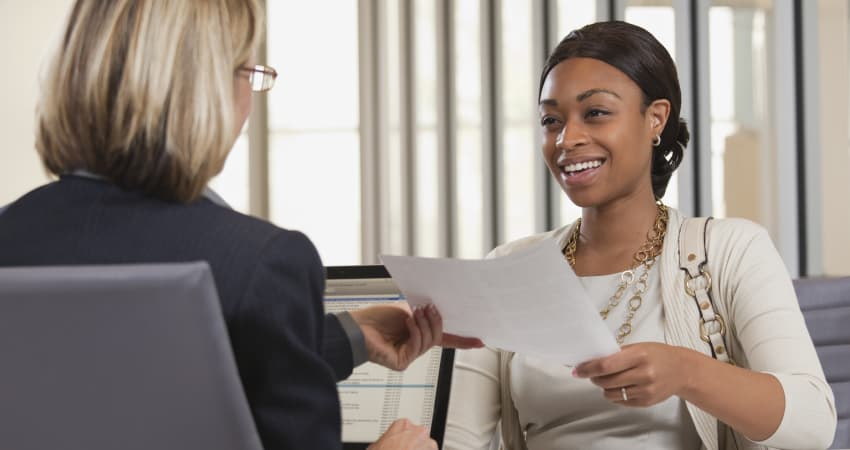A confident candidate hands her resume to her interviewer
