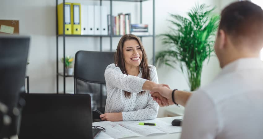 An interviewer and a candidate shake hands across a desk