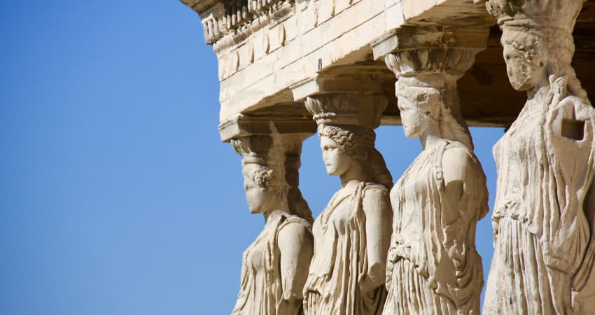 Four crumbling marble statues of women in robes decorate the columns of a Roman ruin, white against a blue sky
