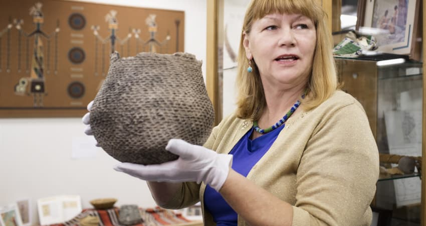 An archivist wearing white gloves holds up an old, woven basket in a museum collections room