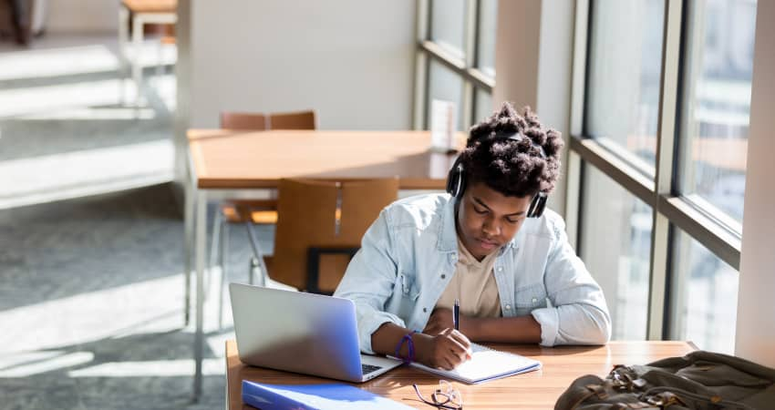 A student with headphones on studies intently at a library desk