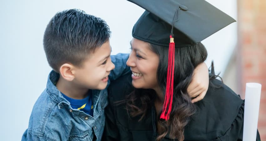 A recent graduate in her cap and gown smiles at her child
