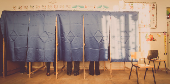 People voting in a classroom.