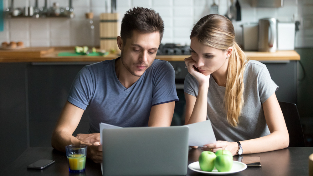 couple in kitchen on laptop looking for student loans