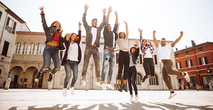 a group of friends jumps up into the air in the middle of a sparse, cobblestoned European plaza.
