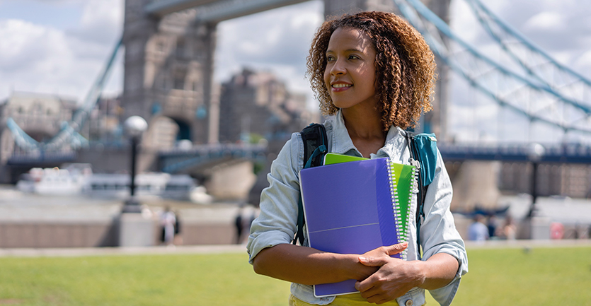 A young woman in a blouse holding several spiral-bound notebooks looks aside, smiling, in front of London Bridge.