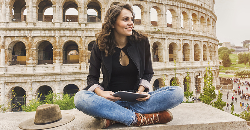 A young womansits cross-legged, tablet in hand, on a ledge overloomking the Coliseum in Rome.