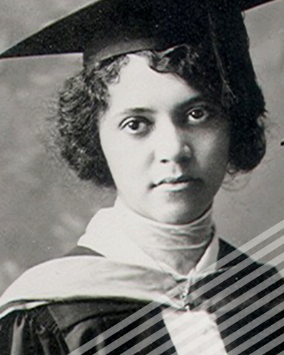 A short-haired Alice Ball wearing a graduation cap and gown looks slightly askance in a black and white photograph.