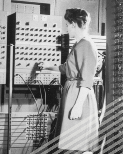 One of the ENIAC programmers adjusts a knob on an enormous early computer.