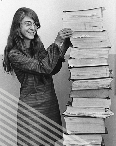 Maragret Hamilton stands next to a stack of code she wrote by hand for the Apollo Project that's almost as tall as she is.