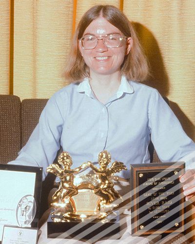 A bespectacled Carol Shaw smiles as she shows off several of awarda for her pioneering video game work.