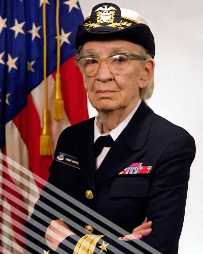 An elderlyGrace Murray Hooper stands in uniform before an American flag.