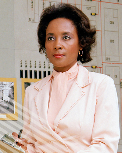 A self-assured Annie Easley in a smart pink blazer takes notes on a clipboard, before a bank of computers.