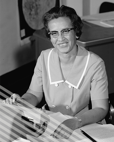 Katherine Johnson  smiles while seated at a desk with a typewriter.
