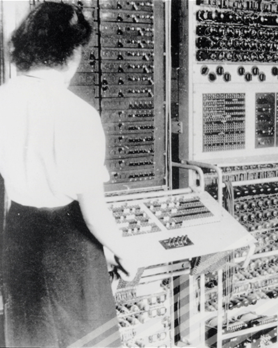 One of the Bletchly Park codebreakers eyes a control panel to a very large, early computer.