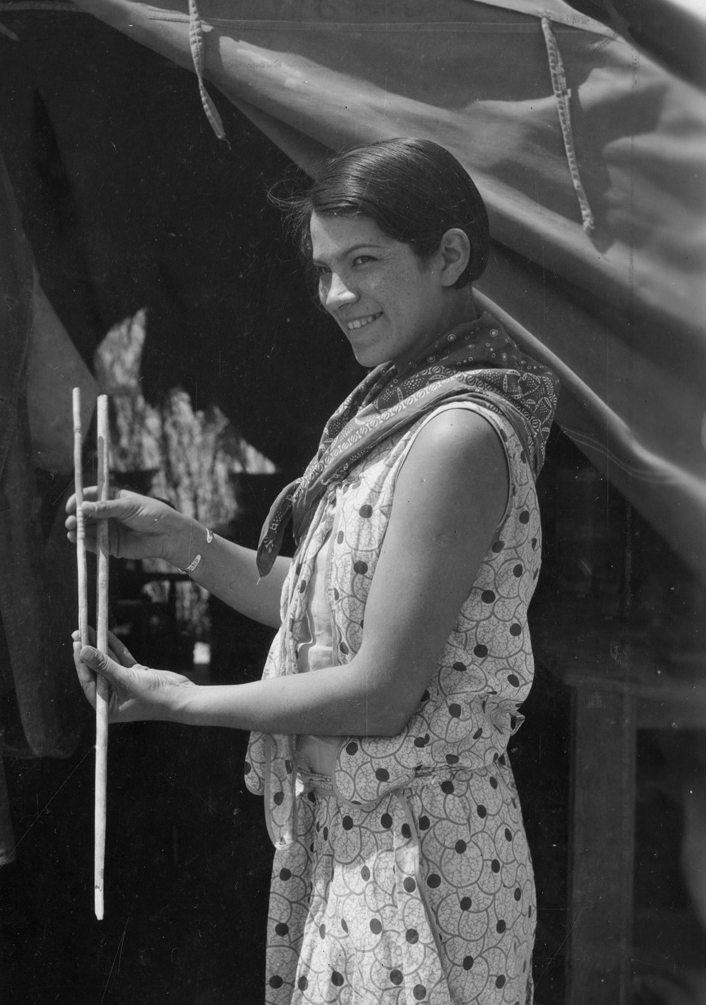 A black and white photograph depicts a young Bertha Parker Pallan Cody holding atlatl darts.