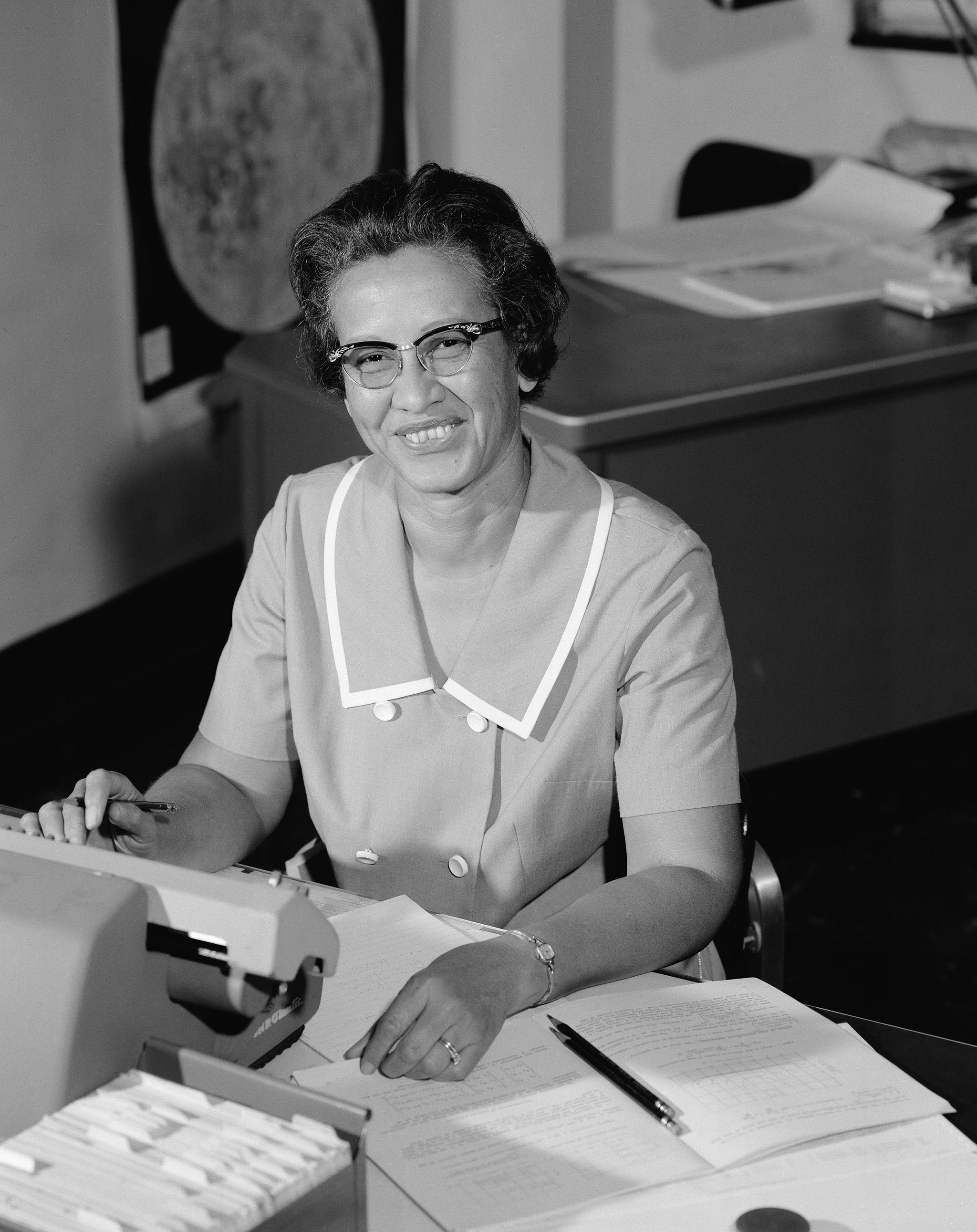 Katherine Johnson smiles while sitting at her desk at NASA.