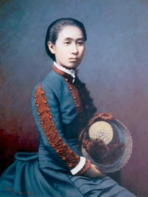 A color photo of Ogino Ginko seated and looking away from the camera, holding her hat in her hands