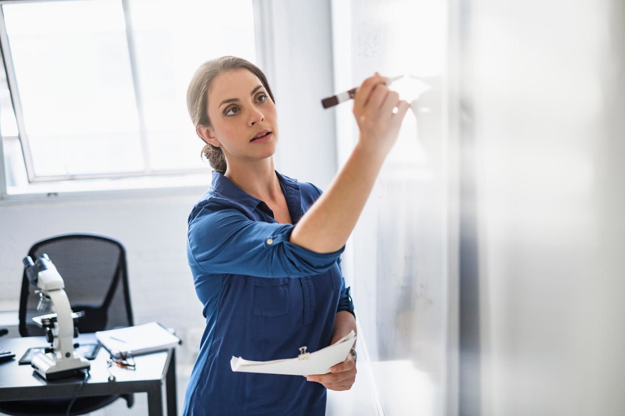 A mid-adult Hispanic female nurse researcher is writing on a whiteboard in her office.