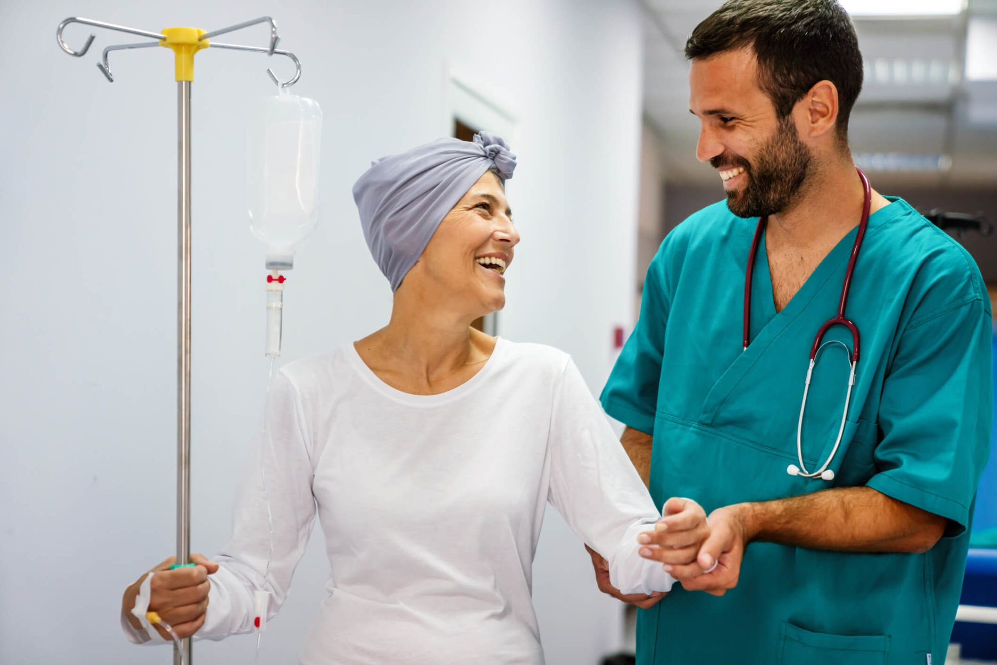 Male nurse assisting an oncology patient as she walks down a hospital hallway.