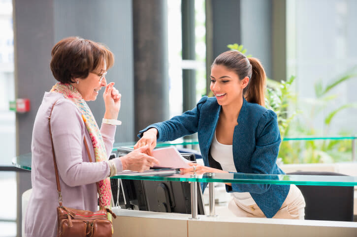 A young female medical assistant is at a hospital reception desk helping a senior patient fill out her check-in forms.