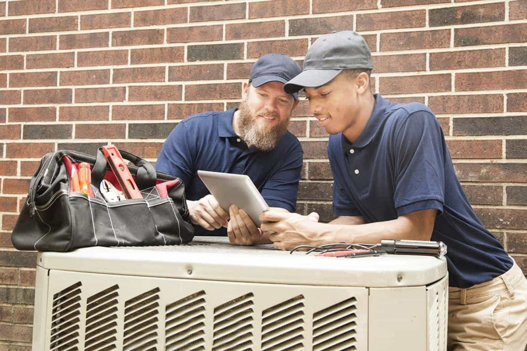 Student apprentice works on an HVAC unit.